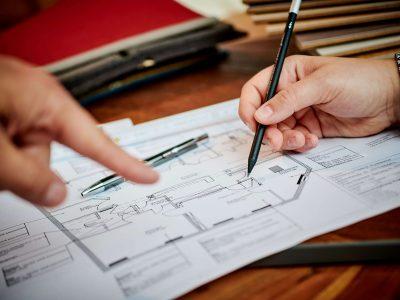 Man sieht zwei Hände, die sich über einem Gebäudeplan befinden. Dort werden gerade neue Dinge eingezeichnet. Das stellt die Beratung bei der Firma Keyser dar.