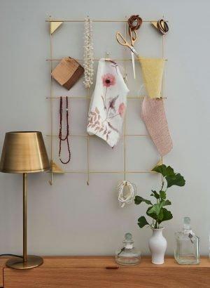 Das Bild zeigt verschiedenen Stoffe, die an einem goldenen Gitter aufgehängt sind, wie bei einer Collage. Daneben steht eine goldene Lampe. Das soll die sorgfältige Auswahl passender Stoffe bei der Firma Keyser symolisieren.