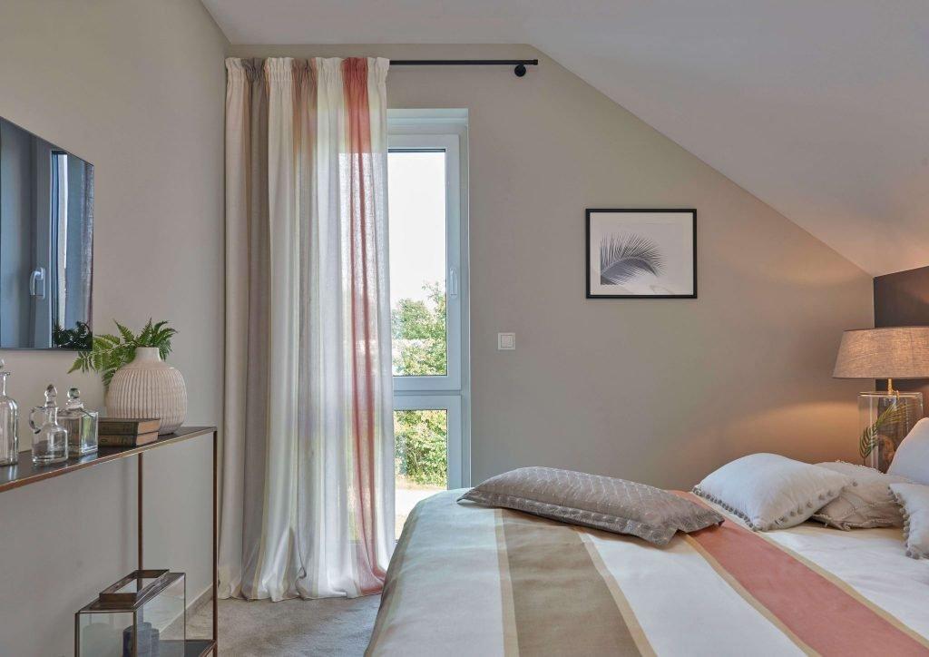 Man sieht ein Schlafzimmer mit einem großen Doppelbett. Im Mittelpunkt steht ein bodentiefes Fenster mit Gardine der Firma Jab Anstoetz,